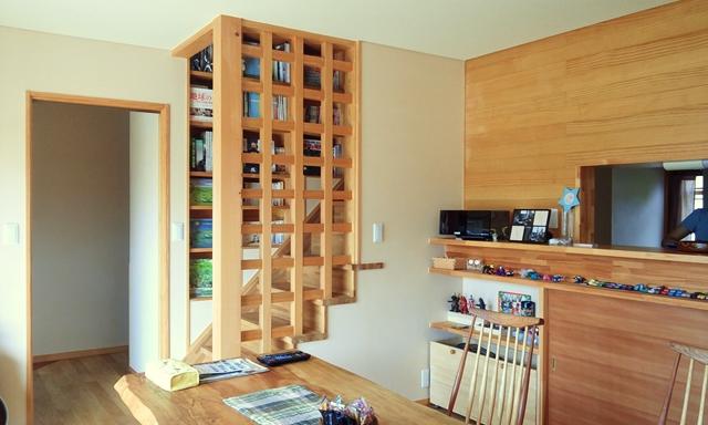 リビング・ダイニングから格子越しに階段脇の本棚を望む